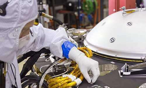 Placing the Mars Chip on the InSight lander's deck in a clean room at Lockheed Martin Space Systems in Denver (Image courtesy of NASA JPL)