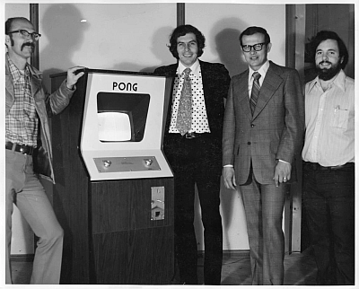 Ted Dabney is seen at the left of a PONG console for arcades shown here in 1973 at the Atari office in Santa Clara, CA with Nolan Bushnell, Fred Marincic and Alan Acorn (left to right from the PONG console) (Image courtesy of Al Acorn, Computer History Museum)